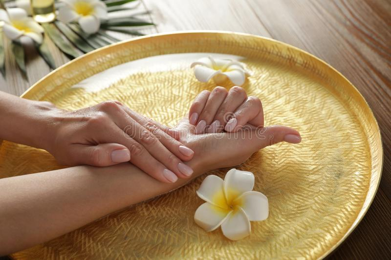 Woman soaking her hands in bowl with water and flowers on table, closeup royalty free stock photography