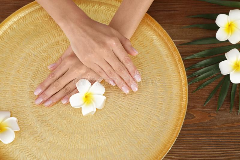 Woman soaking her hands in bowl with water and flowers on wooden table. Spa treatment. Woman soaking her hands in bowl with water and flowers on wooden table stock images