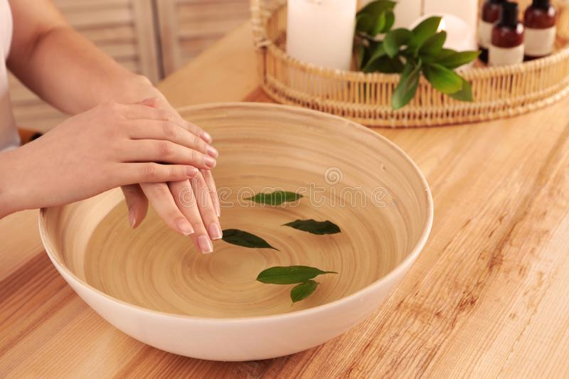 Woman soaking her hands in bowl of water and leaves on wooden table, closeup. Spa treatment. Woman soaking her hands in bowl of water and leaves on wooden table royalty free stock image