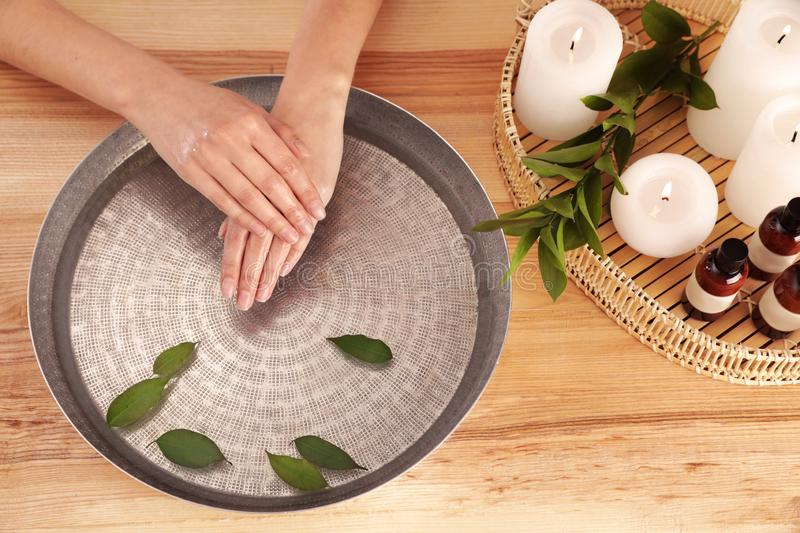 Woman soaking her hands in bowl with water and leaves on wooden table. Spa treatment. Woman soaking her hands in bowl with water and leaves on wooden table, top royalty free stock photo