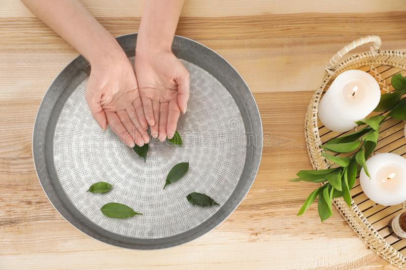 Woman soaking her hands in bowl with water and leaves on wooden table, top view stock photography