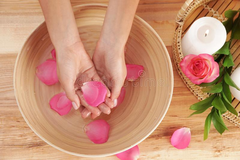Woman soaking her hands in bowl with water and petals on wooden table. Spa treatment. Woman soaking her hands in bowl with water and petals on wooden table, top royalty free stock photos