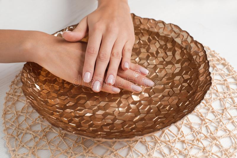 Woman soaking her hands in bowl with water on table. Spa treatment royalty free stock image