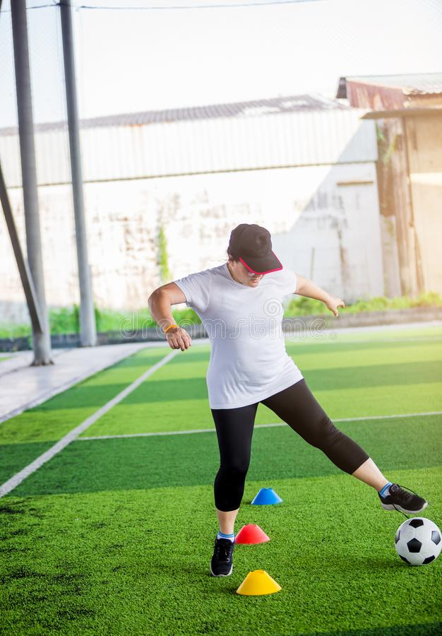 Woman soccer player jogging and control soccer ball between cone markers on artificial turf royalty free stock photography