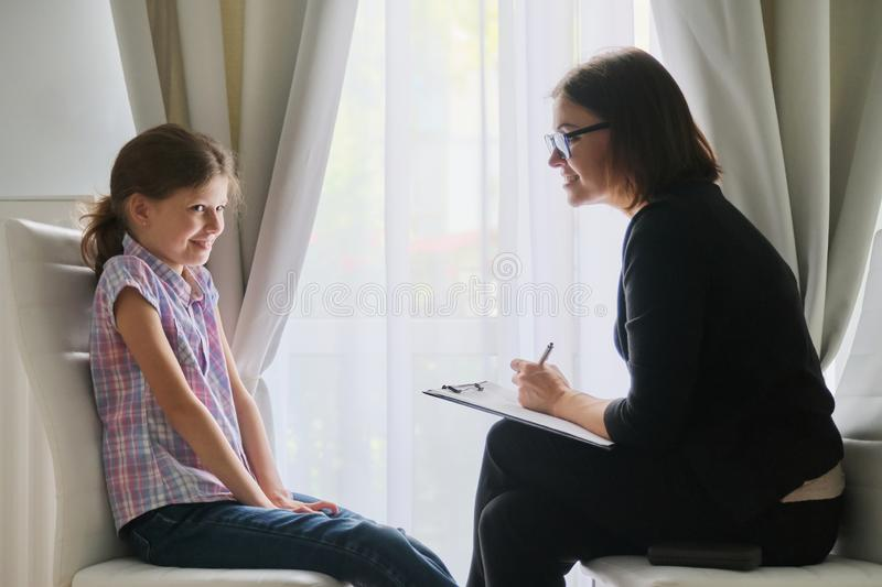 Woman social worker psychologist talking to girl child in office stock photography