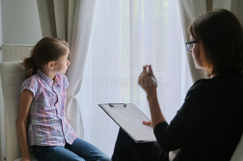 Woman social worker psychologist talking to girl child in office stock images