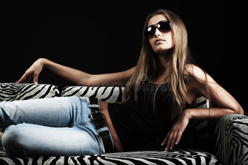 Woman on a sofa. Portrait of a beautiful sexual female model. Beauty, fashion royalty free stock photo