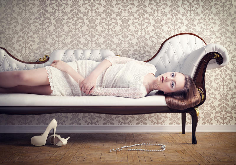 Woman on a sofa. Beautiful young woman relaxing on a vintage sofa stock photo