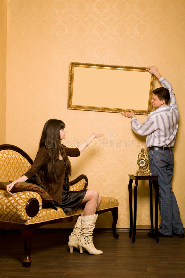 Download Woman On Sofa And Man Hang Up On Wall Picture Stock Photo - Image of decor, improvement: 14577638