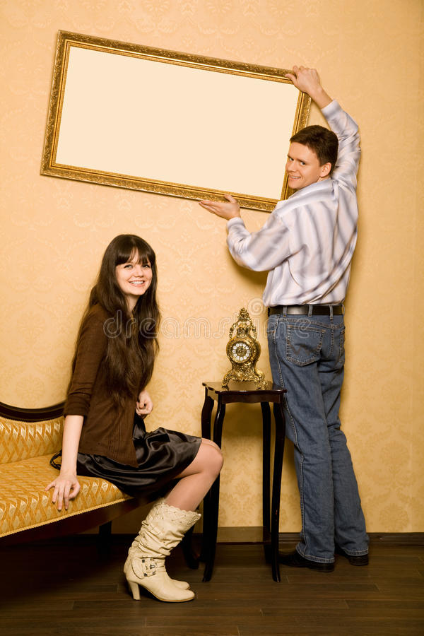 Woman on sofa and man hang up on wall picture. Young beautiful woman sitting on sofa in room and smiling man hang up on wall picture in frame stock photo