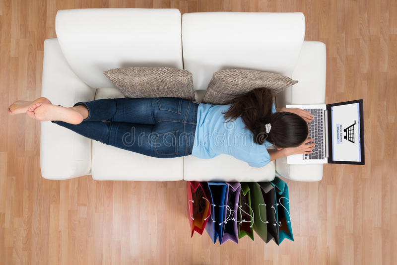 Woman On Sofa Shopping Online With Laptop. High Angle View Of Young Happy Woman On Sofa Shopping Online With Laptop royalty free stock photos
