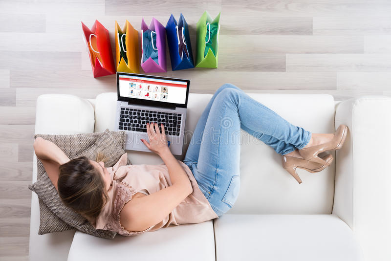 Woman On Sofa Shopping Online With Laptop stock photos