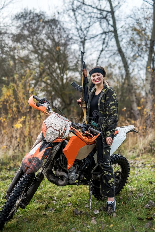 Woman soldier posing with rifle and motorcycle royalty free stock photo