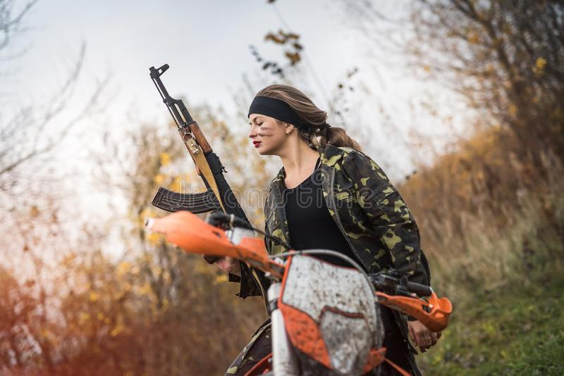 Woman soldier with rifle sitting on motorcycle royalty free stock photos
