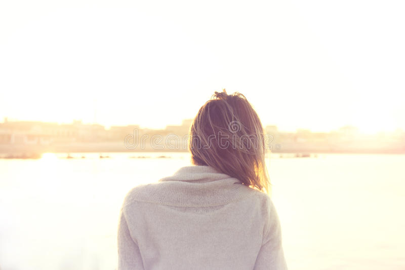 Woman solitary and meditative looking infinity. In front of the sea royalty free stock image