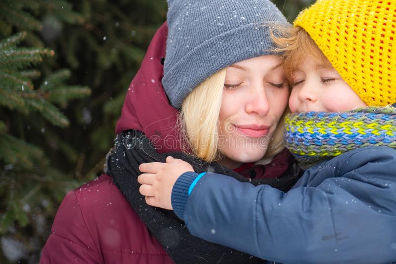 Woman with son smiling snowy winter nature background. Mom and cute child warm hat scarf. Winter fashion concept. Happy stock photo