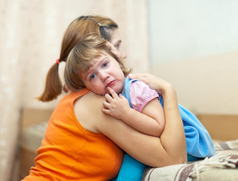 Woman soothes crying daughter stock photography