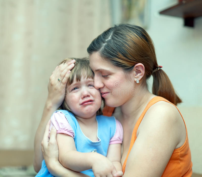 Woman soothes crying daughter stock photo