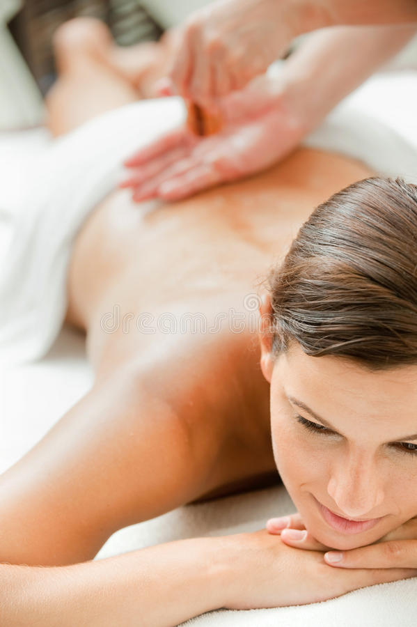 Woman in Spa. An attractive caucasian woman getting massaged in a spa stock photo