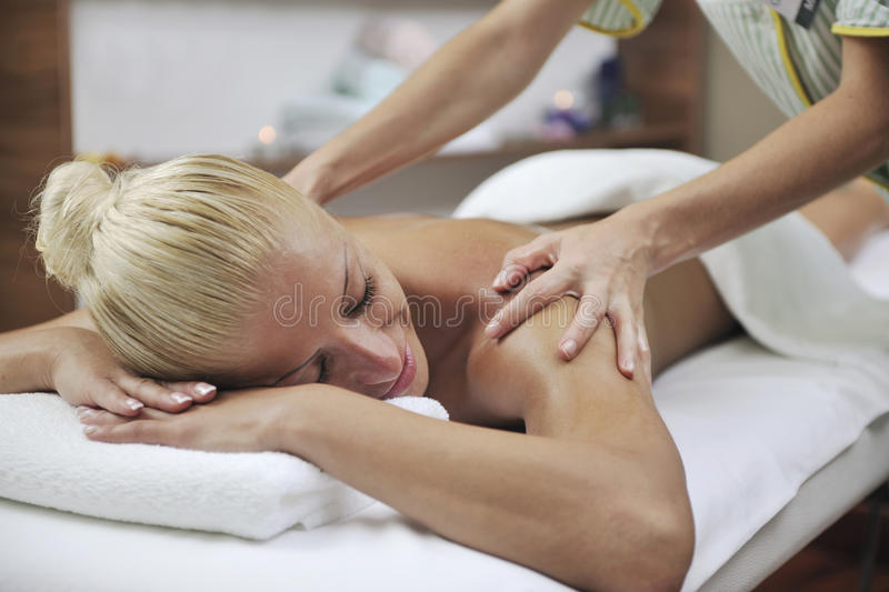 Woman at spa and wellness back massage. Beautiful young woman at spa and wellness back massage treatment royalty free stock images
