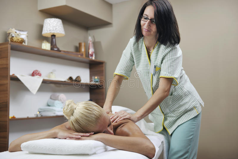 Woman at spa and wellness back massage. Beautiful young woman at spa and wellness back massage treatment stock photos