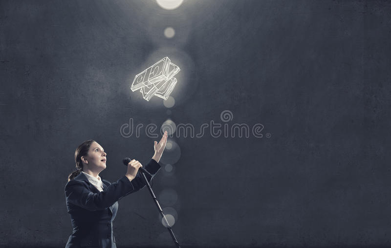Woman speaker. Concept image. Woman reporter with microphone gesturing with hand royalty free stock images
