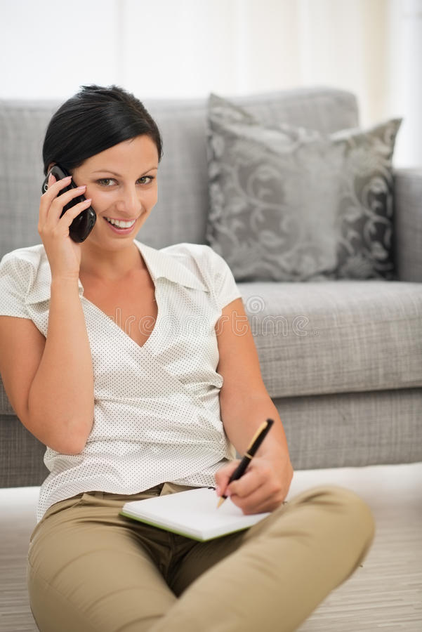 Download Woman Speaking Cell Phone And Writing In Notebook Stock Photo - Image: 27390418