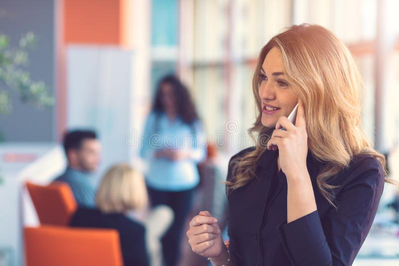 Woman speaking on mobile phone in front of team stock images