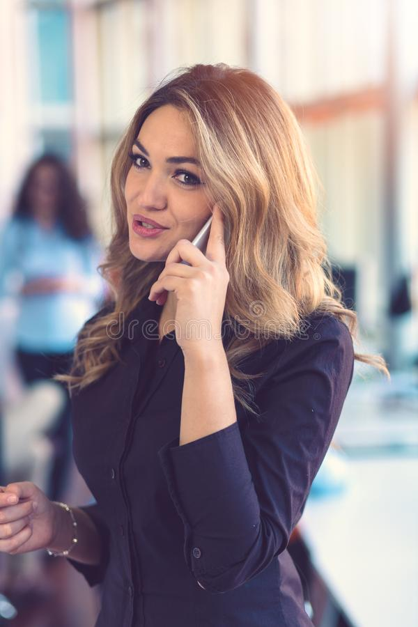 Woman speaking on mobile phone in front of team royalty free stock images