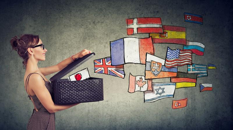Woman speaks different languages opening a box with international flags flying away stock photography