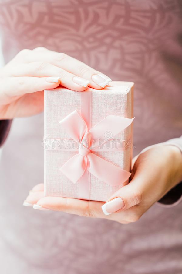 Woman special occasion present lady pink gift box. Woman special occasion present. Cropped shot of lady holding pink gift box with ribbon bow stock images