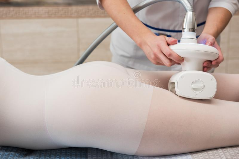 LPG, and body contouring treatment in clinic. Woman in special white suit getting anti cellulite massage in a spa salon. LPG, and body contouring treatment in stock images