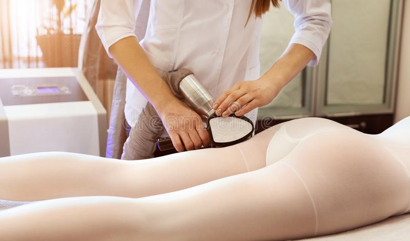 Woman in special white suit getting anti cellulite massage stock photo