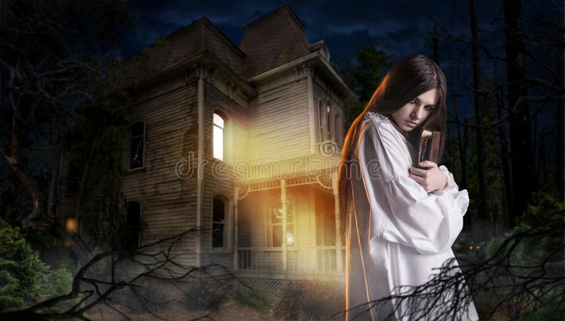 Woman with spellbook, abondoned house in the night. Young woman with spellbook in hand against abondoned house in the night. Dark magic, occultism and exorcism royalty free stock photos