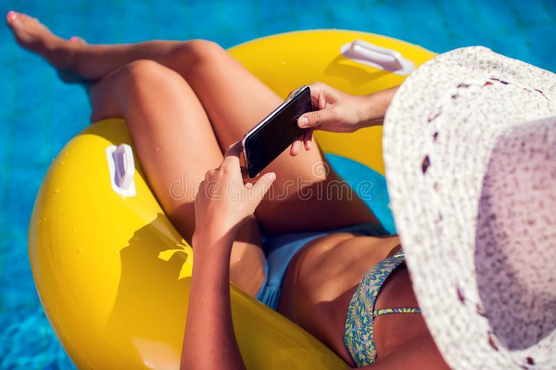 Woman spends time and has relax on the pool with phone. People, summer and holiday concept stock images