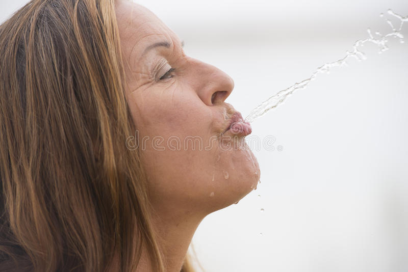 Woman spewing water for fun refreshment. Portrait attractive mature woman spilling, spewing water into the air, with drops running down face, white outdoor stock images