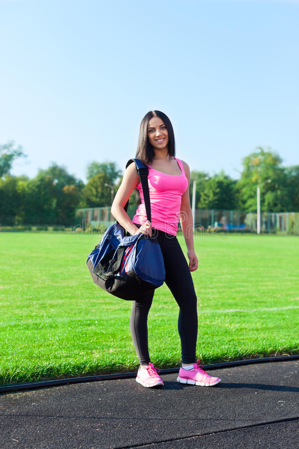 Woman sport bag on stadium outdoors training. Woman sport bag on stadium summer outdoors training, girl morning fitness exercises royalty free stock image