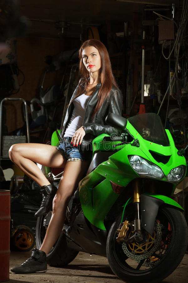 Woman and sport bike. Woman in garage with her sport bike stock photography