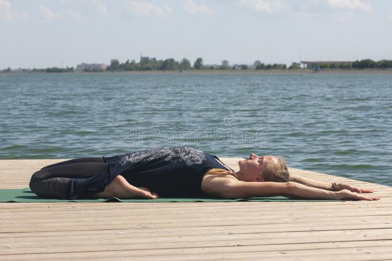 Woman with sport bra doing yoga fitness exercise for relax and healthy at lake in morning, Nature background, Concept outdoor royalty free stock photos