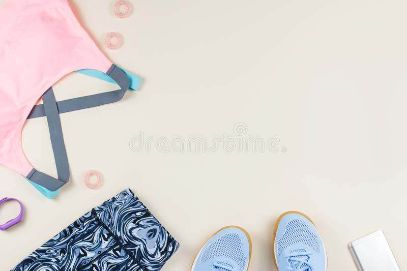Woman sport bra, leggins, sneakers and fitness tracker on neutral background. Sport fashion concept. Flat lay. Top view royalty free stock photos