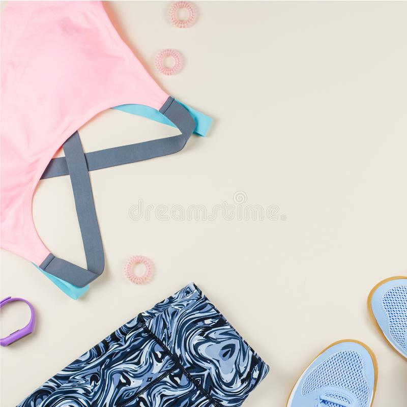 Woman sport bra, leggins, sneakers and fitness tracker on neutral background. Sport fashion concept. Flat lay. Top view royalty free stock photo