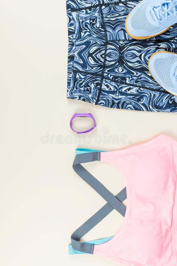 Woman sport bra, leggins, sneakers and fitness tracker on neutral background. Sport fashion concept. Flat lay. Top view stock photography