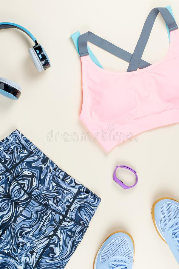 Woman sport bra, leggins, sneakers, headphones and fitness tracker on neutral background. Sport fashion concept. Woman sport bra, leggins, sneakers and fitness royalty free stock photo