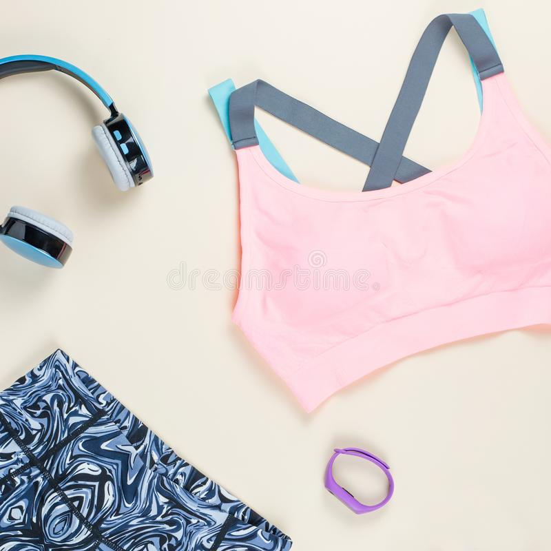 Woman sport bra, leggins, sneakers, headphones and fitness tracker on neutral background. Sport fashion concept. Woman sport bra, leggins, sneakers and fitness stock photography