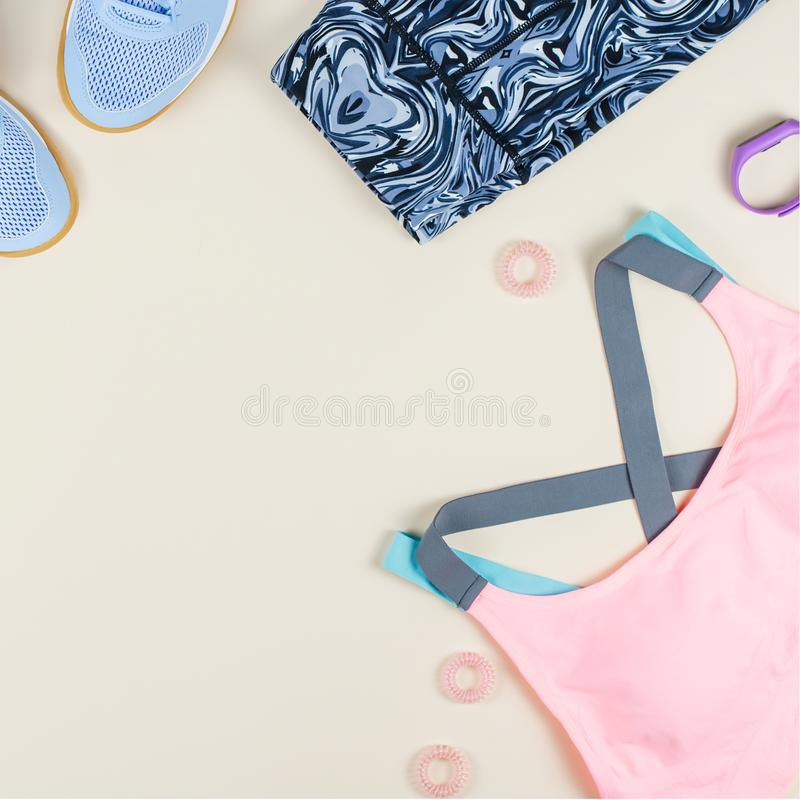 Woman sport bra, leggins, sneakers, headphones and fitness tracker on neutral background. Sport fashion concept. Woman sport bra, leggins, sneakers and fitness royalty free stock image