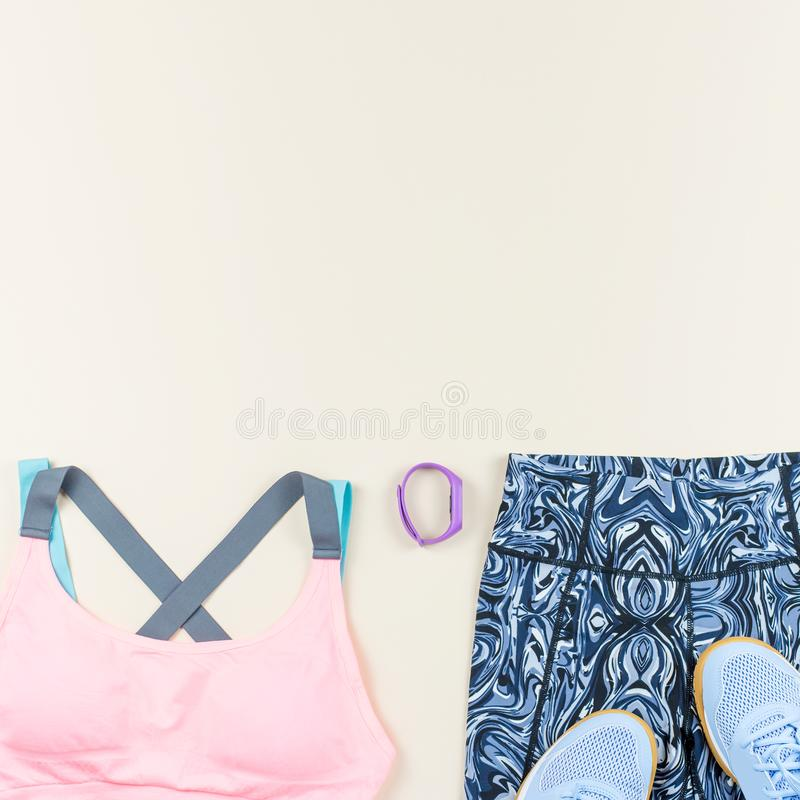 Woman sport bra, leggins, sneakers, headphones and fitness tracker on neutral background. Sport fashion concept. Woman sport bra, leggins, sneakers and fitness stock images