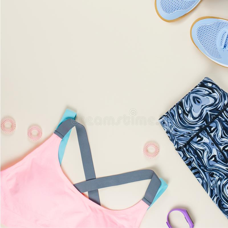 Woman sport bra, leggins, sneakers, headphones and fitness tracker on neutral background. Sport fashion concept. Woman sport bra, leggins, sneakers and fitness royalty free stock photography