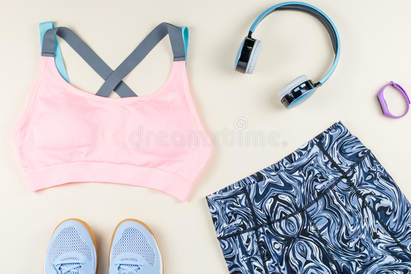 Woman sport bra, leggins, sneakers, headphones and fitness tracker on neutral background. Sport fashion concept. Woman sport bra, leggins, sneakers and fitness stock photos