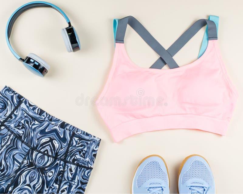 Woman sport bra, leggins, sneakers, headphones and fitness tracker on neutral background. Sport fashion concept. Woman sport bra, leggins, sneakers and fitness stock photo