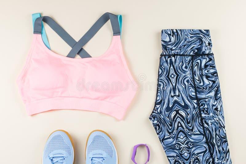 Woman sport bra, leggins, sneakers, headphones and fitness tracker on neutral background. Sport fashion concept. Woman sport bra, leggins, sneakers and fitness stock image
